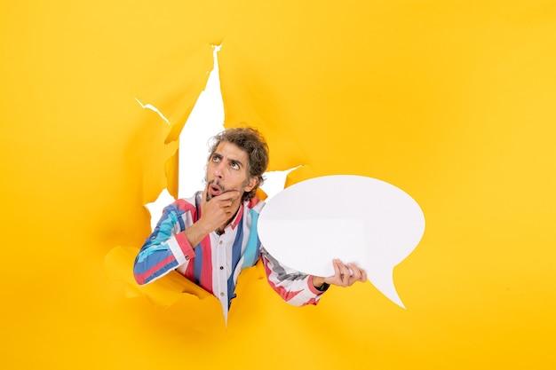 Rozważny młody facet wskazujący białą stronę z wolną przestrzenią w rozdartej dziurze w żółtym papierze