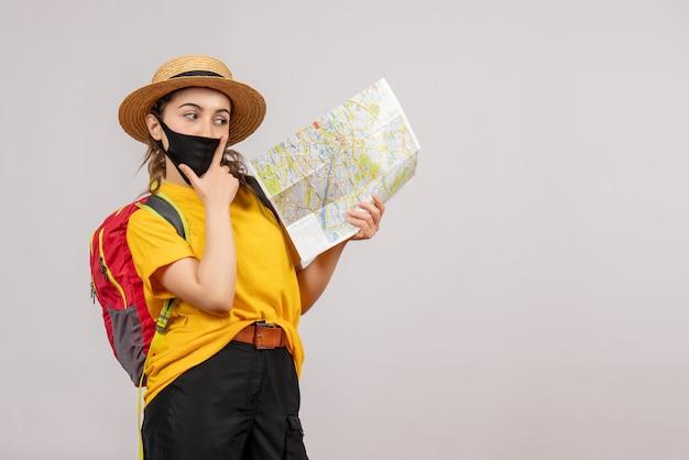 Rozważny młody podróżnik z plecakiem trzymającym mapę na szaro