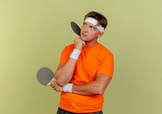 Rozważny młody przystojny sportowy mężczyzna noszący opaskę i opaski, patrząc na bok trzymając rakiety do ping-ponga, kładąc ręce pod brodą i pod łokciem