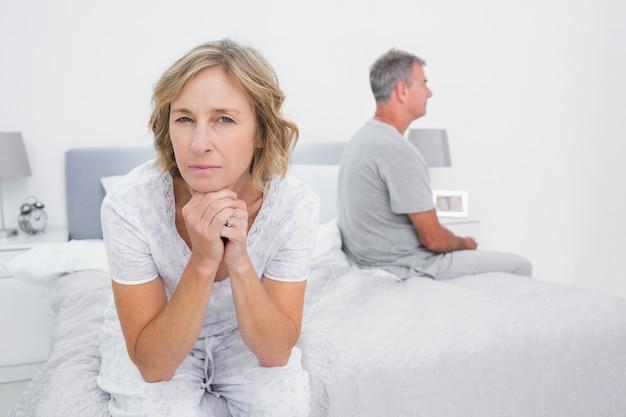 Rozważny pary obsiadanie na różnych stronach łóżko ma spór