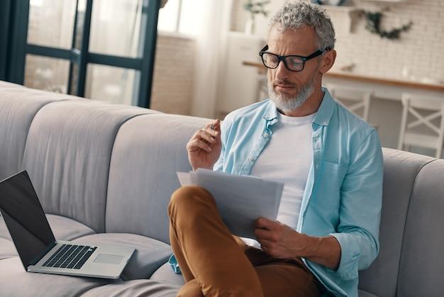 Rozważny starszy mężczyzna sprawdzający dokumenty z poważną miną siedząc na kanapie w domu