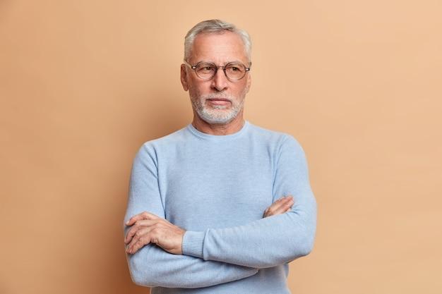 Rozważny, stary, siwowłosy dziadek trzyma założone ręce i odwraca wzrok, zastanawiając się nad czymś ważnym, ubrany w zwykły sweter, pogrążony w myślach, czuje się samotny, gdy żyje samotnie