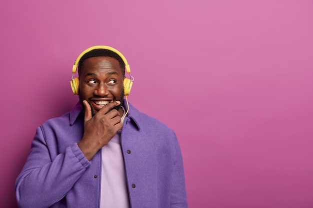 Rozważny szczęśliwy mężczyzna trzyma podbródek, kupił nowe słuchawki do słuchania muzyki, patrzy na bok