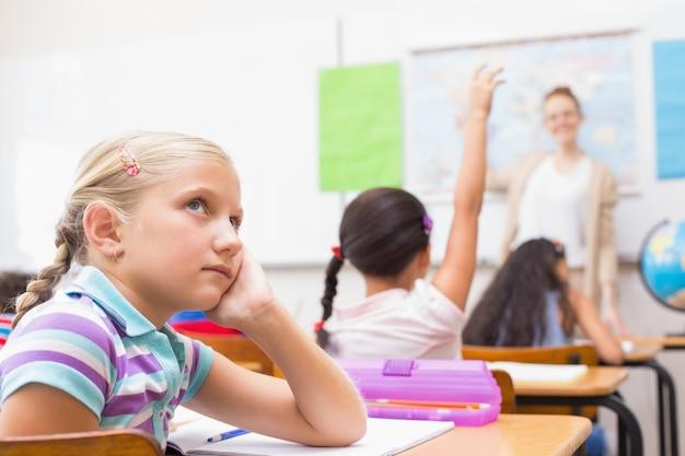 Rozważny uczeń siedzi przy jej biurkiem