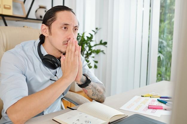 Rozważny, zestresowany grafik składający dłonie w geście modlitwy, patrząc na ekran komputera, zastanawiając się nad rozwiązaniem problemu