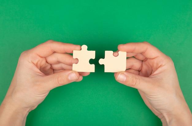 Rozwiązany problem, puzzle z puzzli w ręce na zielonym tle.