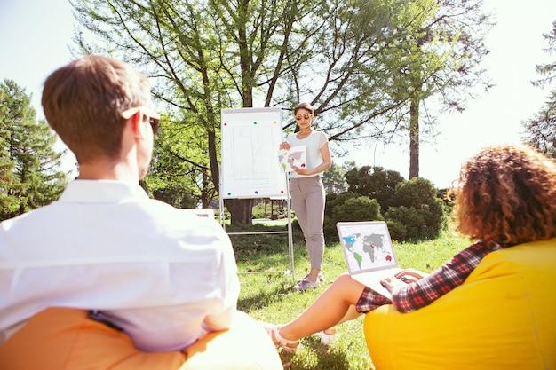 Rozwiązywanie problemu. skoncentrowana, dobrze zbudowana dziewczyna stojąca przy tablicy i omawiająca swój projekt z kolegami z grupy
