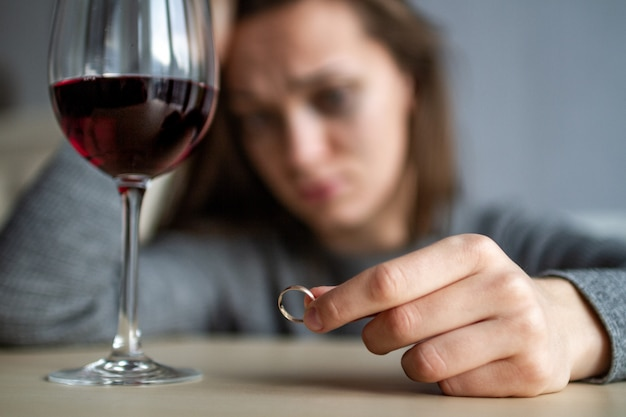 Rozwiedziona kobieta trzyma w rękach obrączkę i pije kieliszek wina