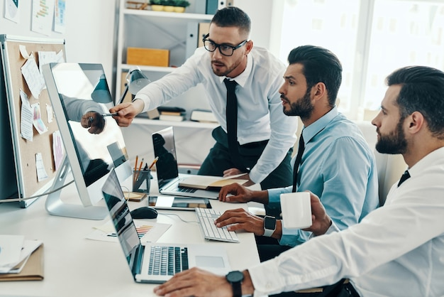 Rozwijanie nowych podejść. grupa młodych, nowoczesnych mężczyzn w strojach formalnych, pracujących przy komputerach, siedząc w biurze