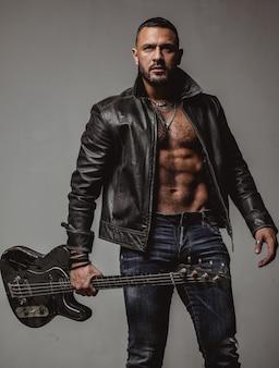 Rozwiń tę imprezę. mięśni lekkoatletycznego seksowny mężczyzna z gitarą. pewny siebie i przystojny brutalny mężczyzna gra muzykę. impreza dla dorosłych. muzyka taneczna. ruszaj ciałem. ciesz się doskonałym dźwiękiem. koncepcja muzyk rockowy.