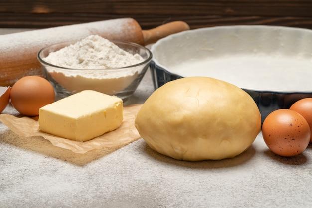 Rozwinięty i nie wypieczony przepis na ciasto kruche na betonowym tle
