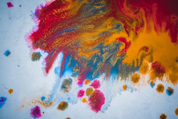 Rozwody i farba kapie na czerwono, pomarańczowo, żółto, niebiesko niewyraźne abstrakcyjne tło na białym tle papieru płaszczyzna zbliżenie makro z efektem tonowania filtra