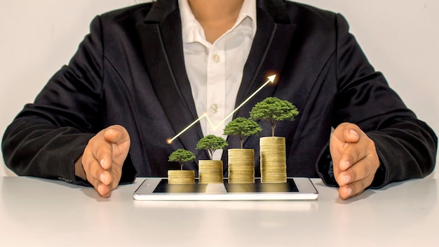 Rozwój finansowy, merchandising online i nowoczesny biznes z drzewem rosnącym na monetach i tabletach.