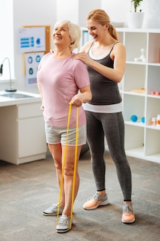 Rozwój mięśni. radosna starsza kobieta trzymająca gumkę, stojąc przed swoim trenerem