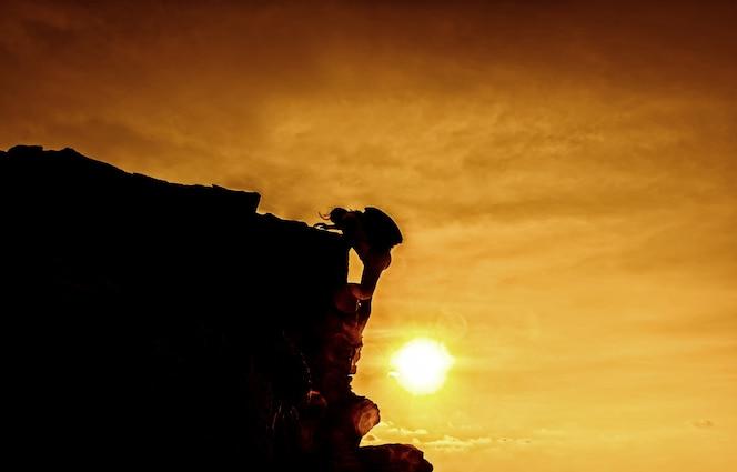 Rozwój osobisty. sukces w biznesie i koncepcja celu. wspinacz sylwetka na klifie.