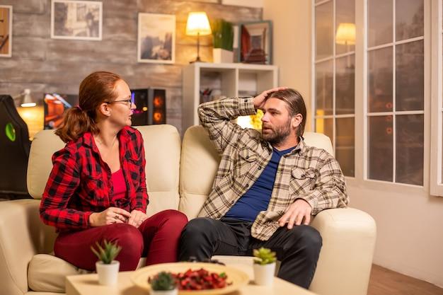 Rozzłoszczeni i sfrustrowani gracze przegrywają późną nocą podczas grania w gry wideo w salonie