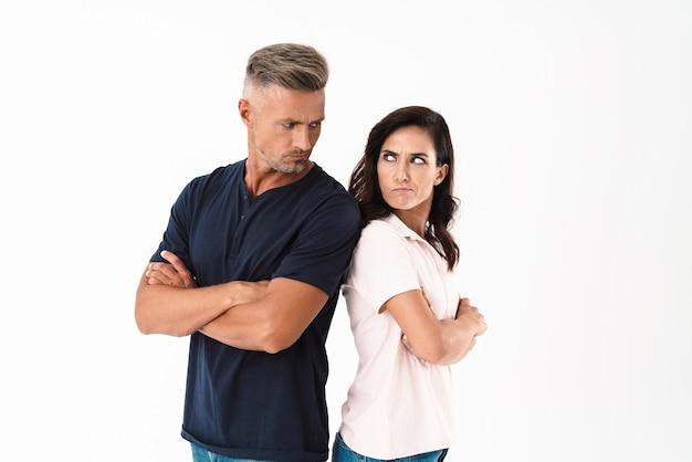 Rozzłoszczona atrakcyjna para w stroju casual, stojąca na białym tle nad białą ścianą, z założonymi rękoma