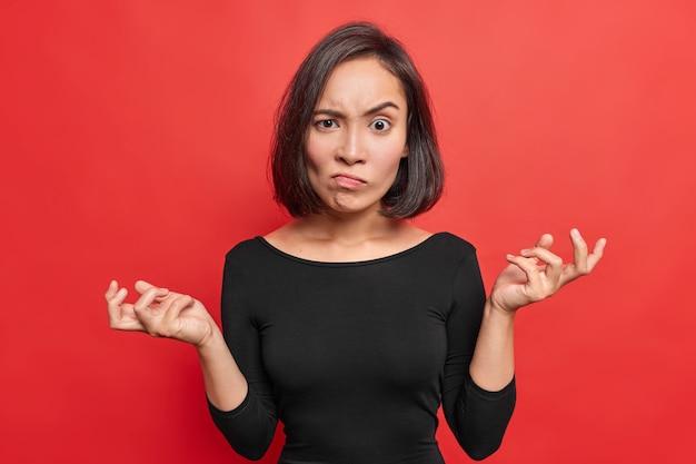 Rozzłoszczona azjatka unosi brwi z irytacji, trzyma dłonie na boki, z wahaniem wzrusza ramionami, ma na sobie czarny sweter na tle jaskrawych, czerwonych ścian ze zdumieniem.
