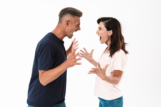 Rozzłoszczona para w swobodnym stroju stojąca na białym tle nad białą ścianą, kłócąca się