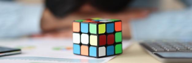 Rubik jest sześcianem na stole ze zmęczoną kobietą w tle wyjście z koncepcji rozpaczliwych sytuacji