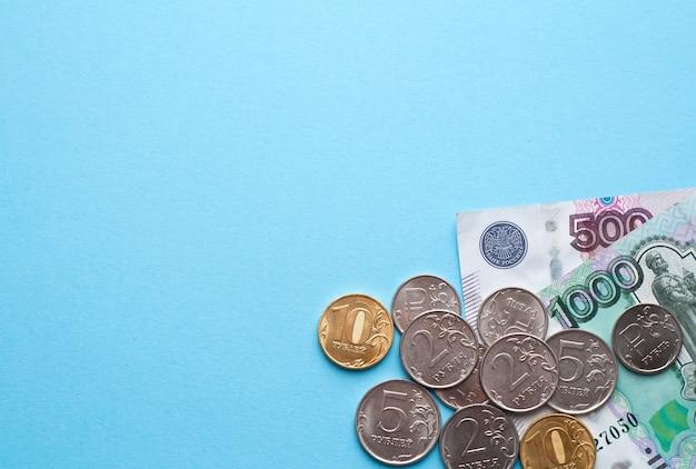 Ruble rosyjskie na niebieskiej ścianie. tysiące banknotów i różne monety. miejsce na tekst.