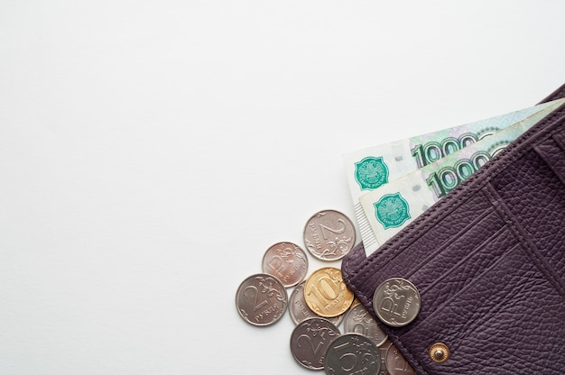 Ruble rosyjskie w portfelu na białej ścianie. tysiące banknotów i różne monety. miejsce na tekst.