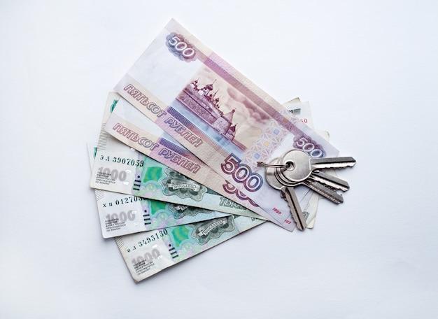 Rubli rosyjskich banknoty i klucze do domu na białym tle