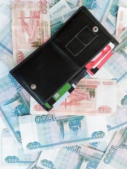 Rubli rosyjskie kategorii tysiąc i pięć tysięcy z otwartym portfelem na nich.