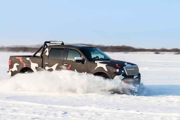Ruch czarnej amerykańskiej ciężarówki zamazany podczas szybkiego poruszania się po śniegu