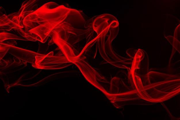 Ruch czerwony dym na czarnym tle. ogień