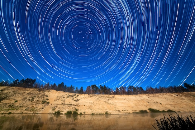Ruch gwiazd wokół gwiazdy polarnej na tle rzeki