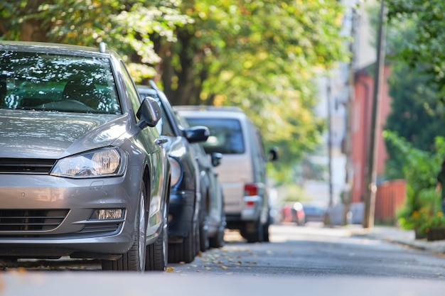 Ruch miejski z samochodami zaparkowanymi w kolejce po stronie ulicy.
