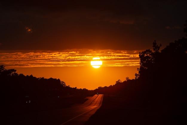 Ruch na autostradzie o zachodzie słońca. droga z metalową barierą bezpieczeństwa. samochody na asfalcie pod zachmurzonym niebem.
