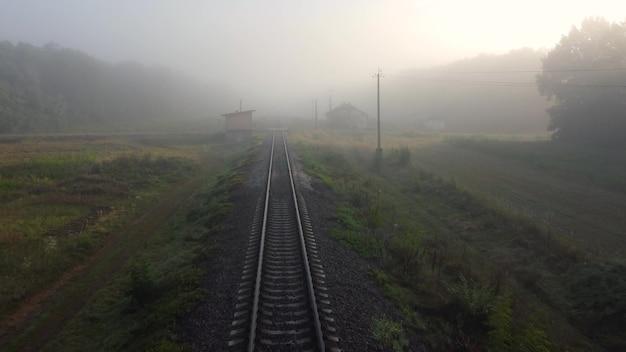 Ruch na torach, poranna jesienna mgła, słońce przeświecające przez mgłę na drodze.