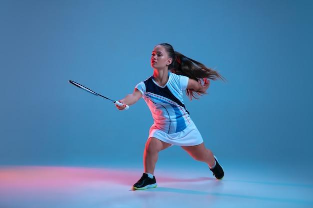 Ruch. piękna mała kobieta ćwicząca w badmintonie na niebieskim tle w neonowym świetle
