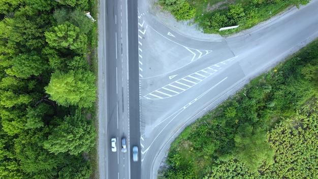 Ruch samochodów po asfaltowej drodze pomiędzy zielenią drzew, widok z lotu ptaka na skrzyżowanie nierównych dróg