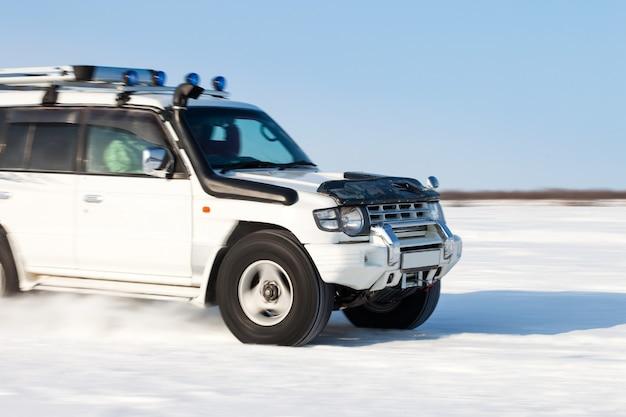 Ruch samochodu terenowego zamazany podczas szybkiego poruszania się po śniegu