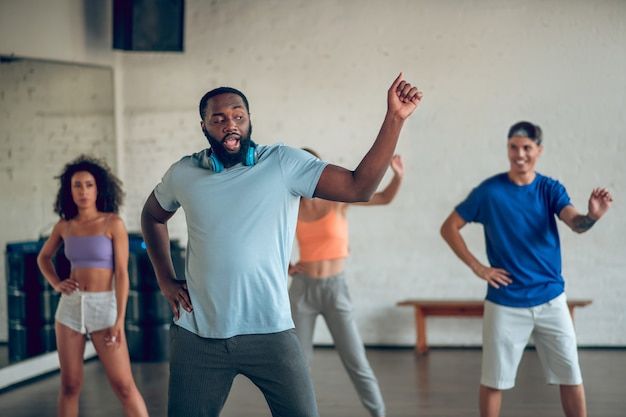 Ruch taneczny. młody brodaty ciemnowłosy mężczyzna ze słuchawkami na szyi podczas próby tańca razem z przyjaciółmi