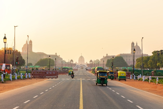 Ruch uliczny o zachodzie słońca w new delhi, samochody na drodze do prezydenckiej rady.