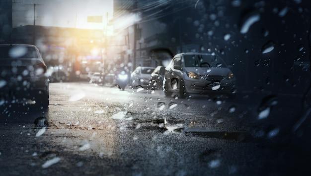 Ruch w deszczowy dzień z wieczornym światłem w mieście, widok przez przednią szybę podczas burzy z selektywnym focusem.