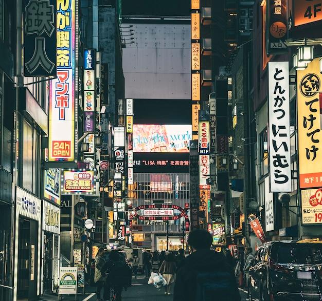 Ruchliwa ulica w mieście w nocy z ludźmi i znakami