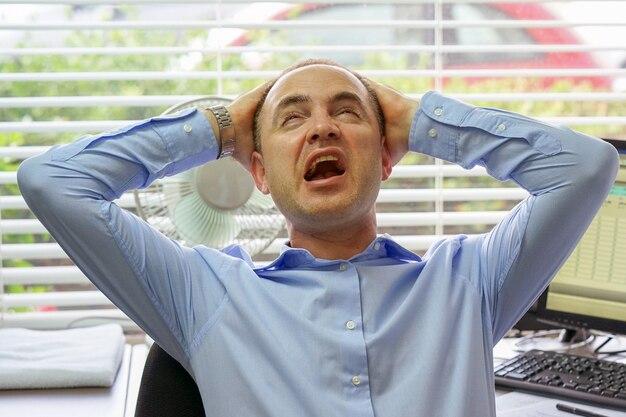 Ruchliwie biznesmen ma stres i migrenę przy biurem.