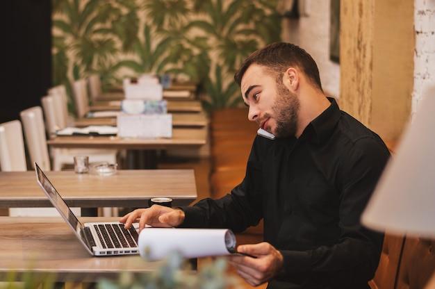 Ruchliwie przystojny mężczyzna pracuje od kawiarni