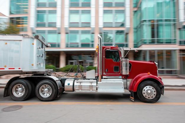 Ruchoma czerwona ciężarówka przewożąca przyczepę na ulicy