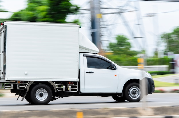 Ruchomy obraz, mała biała ciężarówka poruszająca się po drodze dla biznesu logistycznego.