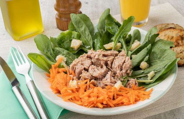 Rucula, tuńczyk, parmezan i sałatka z marchwi z oliwą i sokiem pomarańczowym.