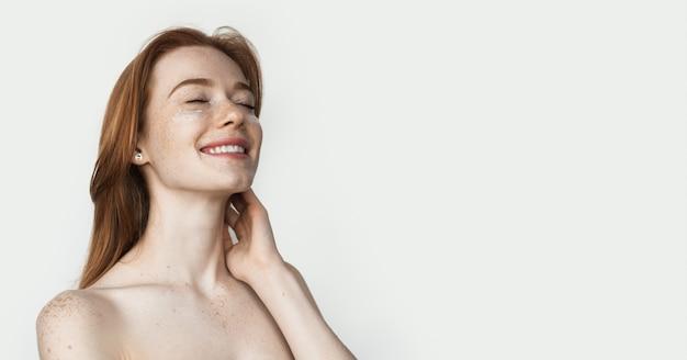 Ruda dama z piegami ma na sobie przeciwstarzeniowe opaski na oczy, pozując na białej ścianie studia z nagimi ramionami coś reklamującego
