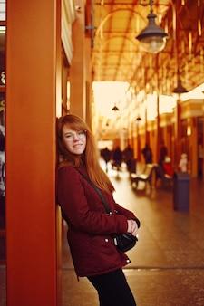 Ruda dziewczyna czeka pociąg na peronie dworca kolejowego