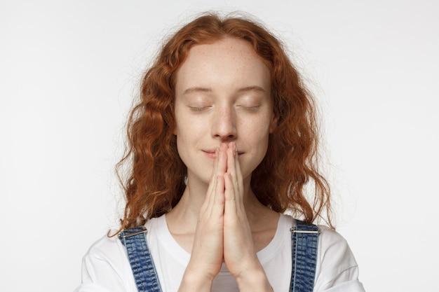 Ruda dziewczyna modli się i uśmiecha z zamkniętymi oczami