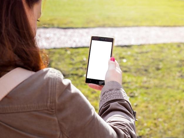 Ruda dziewczyna na zewnątrz za pomocą smartfona. biały ekran. wiosna